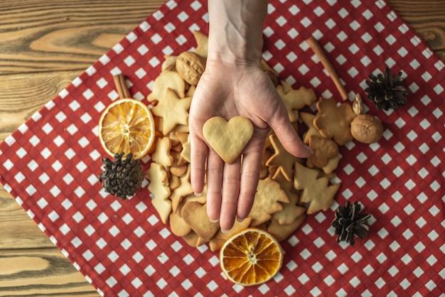 빨간 식탁보에 수제 쿠키 더미가 있고 여자의 손이 하트 모양의 쿠키 하나를 들고 있습니다