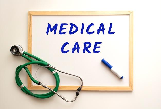 На белой доске есть стетоскоп и написано слово. медицинская концепция.