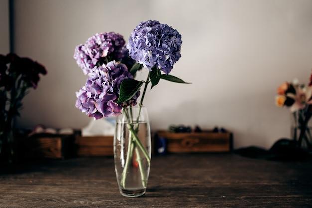木製のテーブルの上に青とライラックのアジサイの花瓶があります。