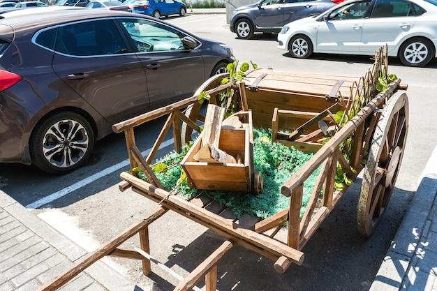 車の隣の駐車場に木製のカートがありますお祭りの装飾と装飾