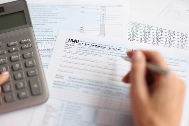 На столе концепции налоговой декларации есть индивидуальный документ налогового вычета и калькулятор.