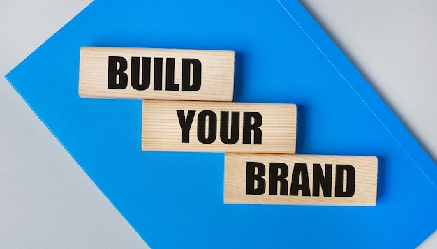There is a blue notebook on a light gray background. above are three wooden blocks with the words build your brand.