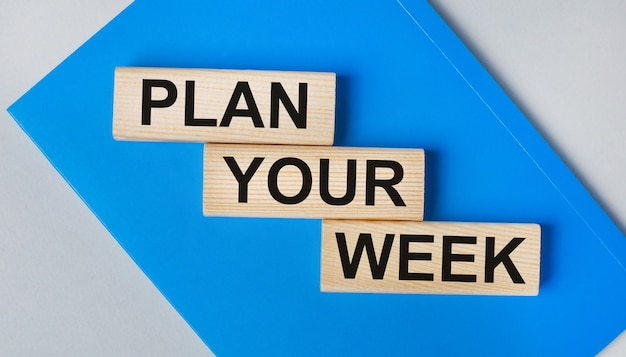 There is a blue notebook on a light gray background. above are three wooden blocks with the words plan your week.
