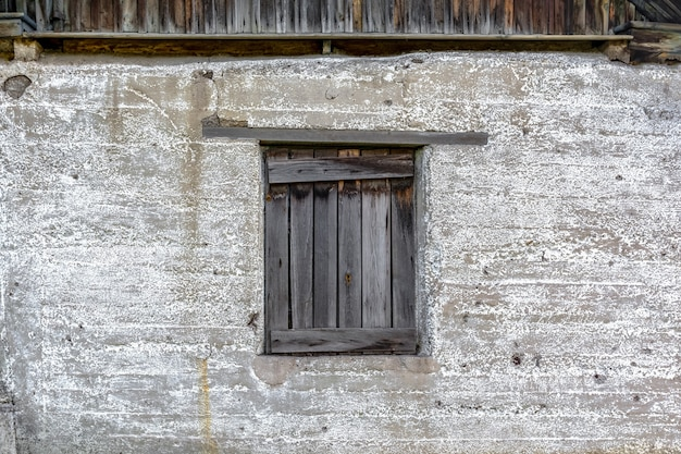 There is a boardedup wooden window on the old weathered concrete wall an abandoned village barn