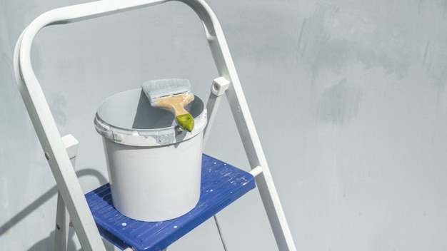 There is a bucket of paint and a paintbrush on the stairs against the background of a blue repair wall.