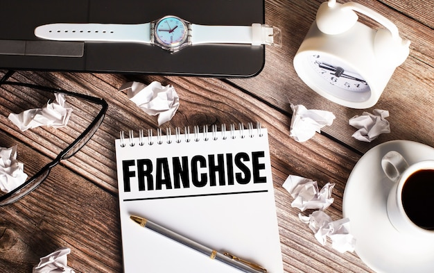 There is a cup of coffee on a wooden table, a clock, glasses and a notebook with the word franchise. business concept