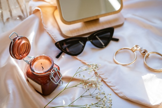 There is a decorative candle in a jar on the fabric black glasses and jewelry with a mirror soft focus