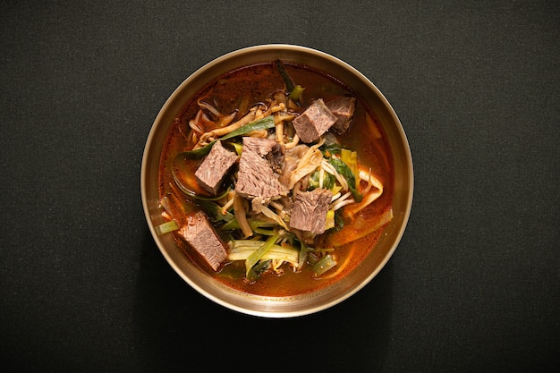There is meat soup in a bowl the background is black texture