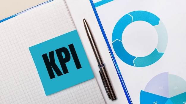 There is a pen between the blue sticky note with the text kpi and the blue chart. business concept. view from above