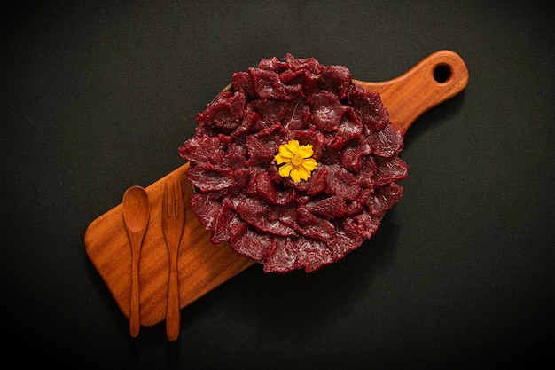 There is raw beef on a wooden plate the background is black texture