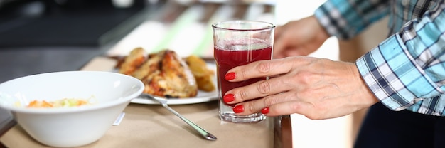There is salad on tray and a second dish woman's hand holds glass with red liquid.
