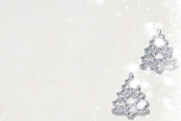 There is a small silver tree on a white background.