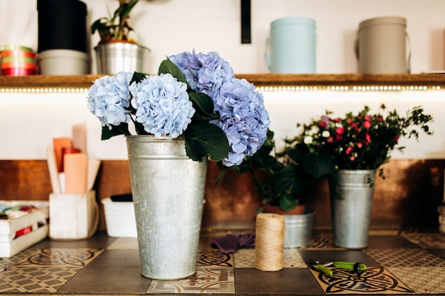 There is a vase with light blue hortensia on the table in the flower shop .