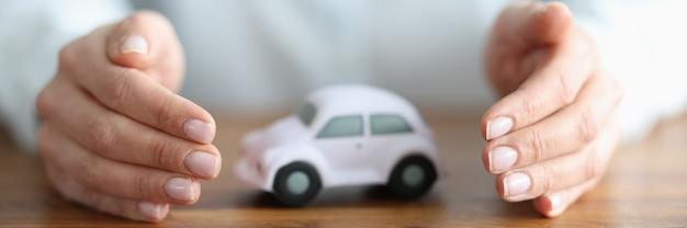 女性の手の中に白い車があります。自動車保険と保証サービスのコンセプト