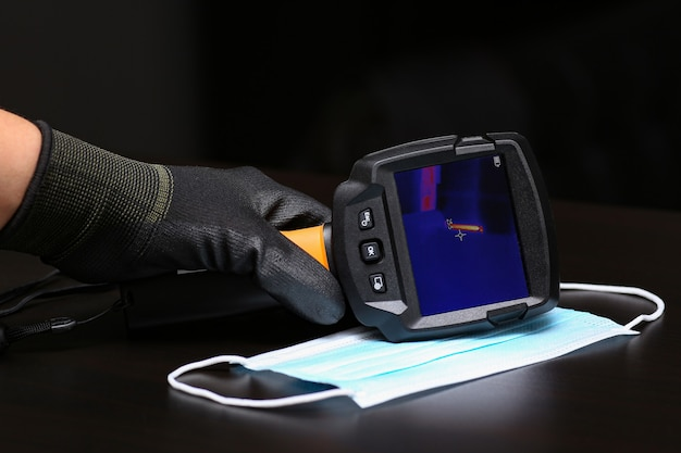 The thermal imager inspection camera and protective mask lie on the surface to check the temperature of people