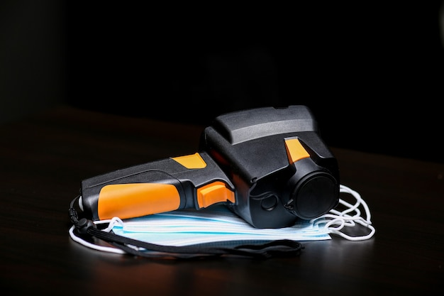 The thermal imager inspection camera and protective mask lie on the surface