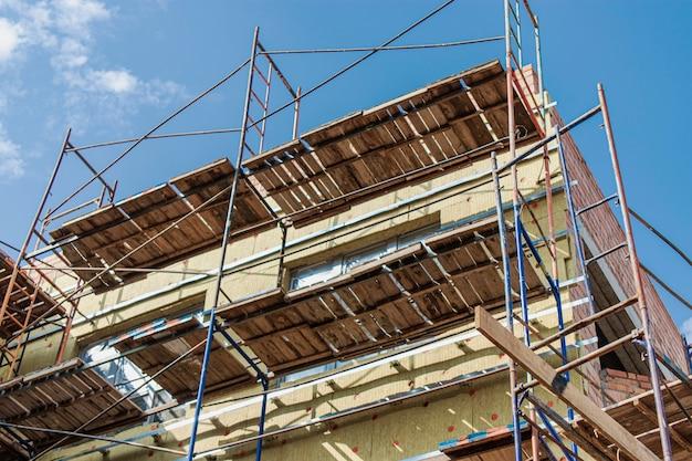 Утепление дома из красного кирпича минеральной ватой. использование строительных лесов при строительстве дома.