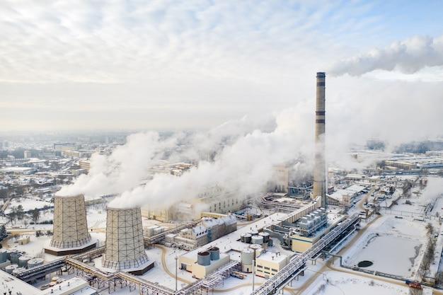 Теплоэлектростанция зимой в минске. дым идет из больших дымоходов.