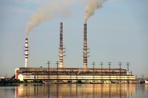 Thermal power station tall pipes with thick smoke reflected in lke water surface. pollution of environment .