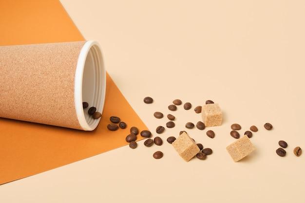 Термокружка, разбросанные кофейные зерна и кубики коричневого тростникового сахара на коричневом и бежевом геометрическом фоне с копией пространства