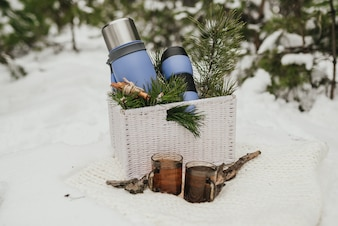 Thermocup, thermos with cup of tea and pine branches lying in a basket
