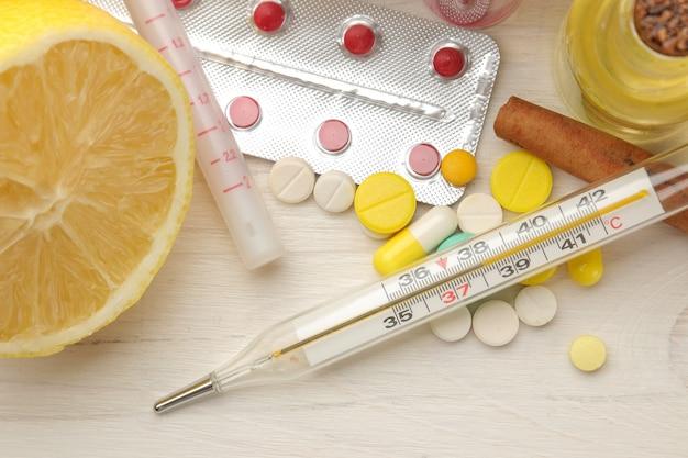 흰색 나무 테이블에 독감과 감기에 대한 온도계 및 각종 의약품