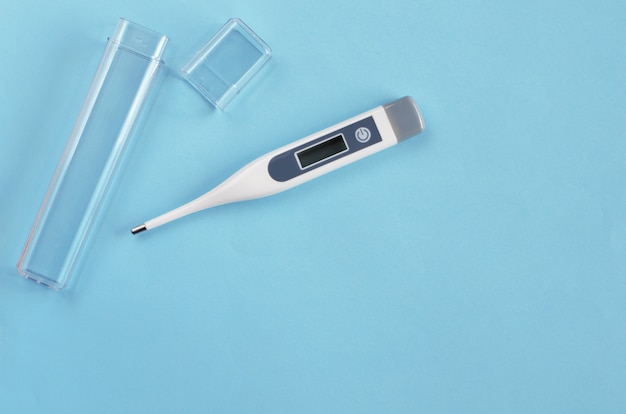 Thermometer on blue . top view. copyspace. healthcare