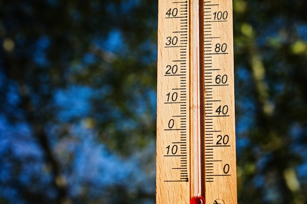 Thermometer displaying high 30 degree hot temperatures in sun summer day.
