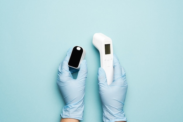 Thermometer and electronic pulse oximeter in the hands of a doctor, wearing blue latex gloves, close up