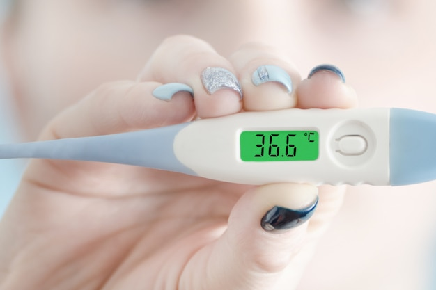 Thermometer in female hand. normal body temperature.