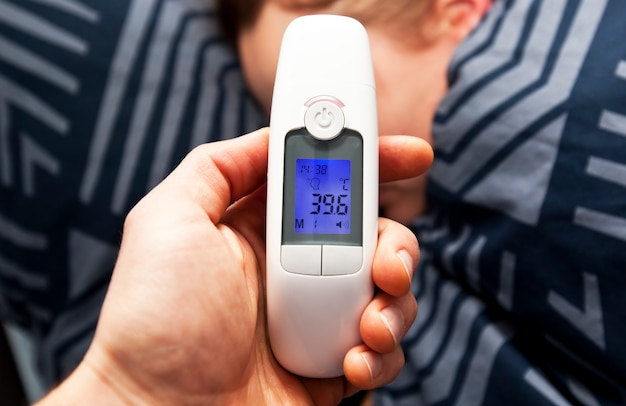 A thermometer in a man's hand that shows high temperature in his wife