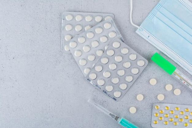 Termometro, maschera, siringa e pillole mediche su fondo di marmo. foto di alta qualità