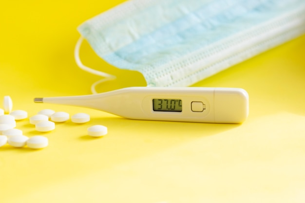 Thermometer, medical mask and medical pills, tablets on light background.