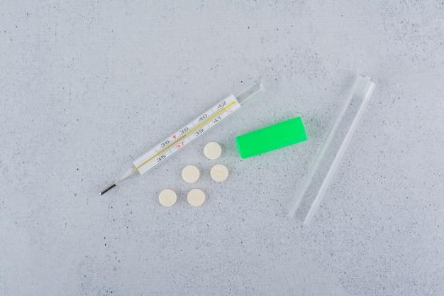 Termometro e pillole mediche su sfondo marmo.