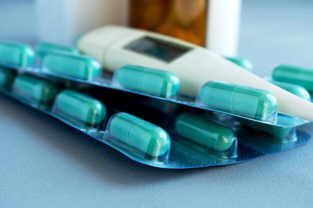 青い背景の温度計、薬や錠剤。医療医師の概念。