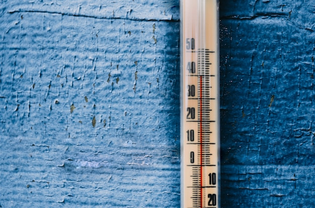 Thermometer on the old wooden wall, concept of hot weather.