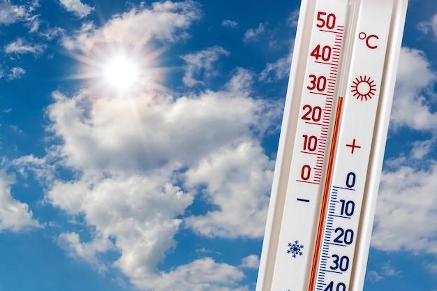 白い雲と太陽と青い空を背景にした温度計は30度の熱を示しています。夏の暑さ