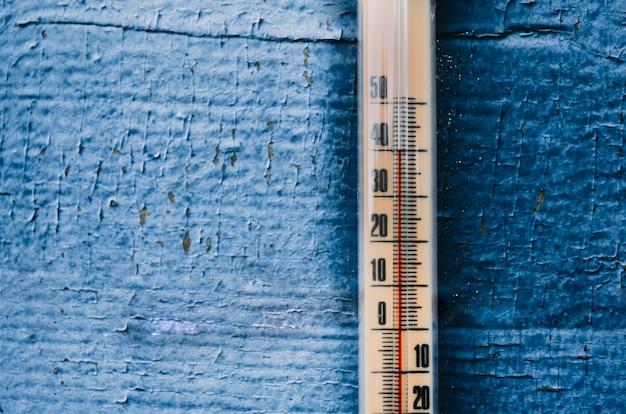 古い木製の壁、暑さの概念の温度計。