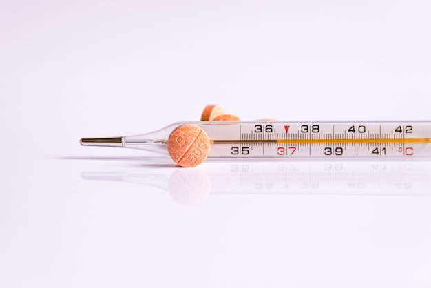 A thermometer and vitamins on a white background.