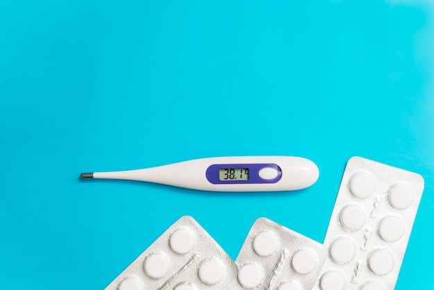 Thermometer with high temperature and medicines pills on a blue background