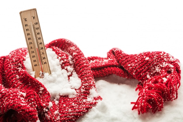 Thermometer with sub zero temperature sticks out in a snowdrift wrapped red scarf