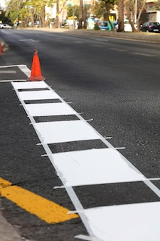 Thermoplastic road marking tape painting traffic lines and bike lanes on asphalt road surface sele