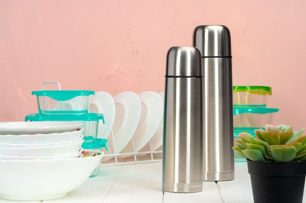 Thermos bottle against tableware in a kitchen