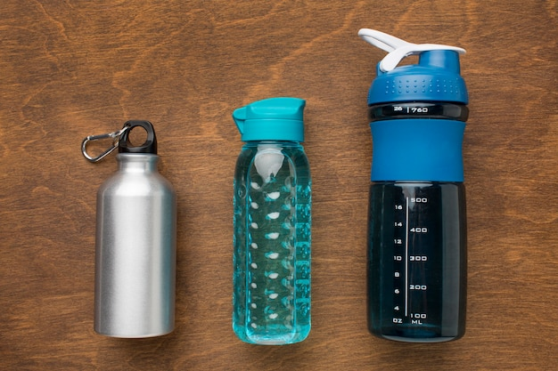 Thermos and fitness bottles of water top view