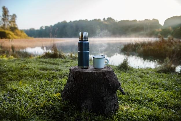 호수 배경에 뜨거운 음료와 보온병 머그잔.
