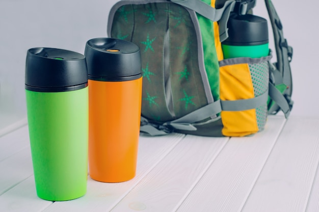 Thermos mugs in front of the backpack