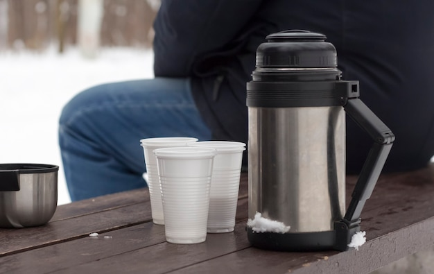 자연에서 티 파티 후 겨울에 벤치에 컵과 보온병.
