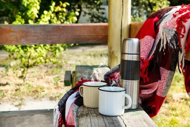 Термос с горячим чаем на деревянном столе.