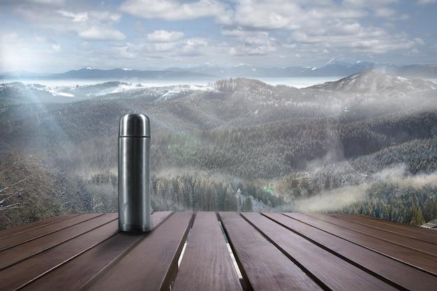 Термос с чаем или кофе и пейзаж гор на фоне. горячий напиток, туман и облачное небо перед ним. теплый зимний день, праздники, путешествия, приключения, время празднования.