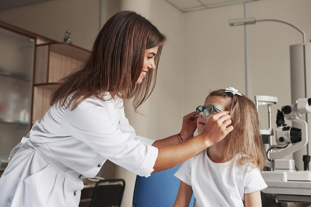 Эти устройства подходят вам. маленькая девочка пробует новые синие очки в офтальмологическом кабинете с женщиной-врачом.